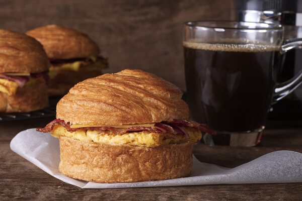 Bacon, Egg, and Gouda Cheese on Croissant Bun, P140. Crispy honey-cured bacon, fluffy egg patty, and melted aged gouda cheese are stuffed into their signature croissant bun.