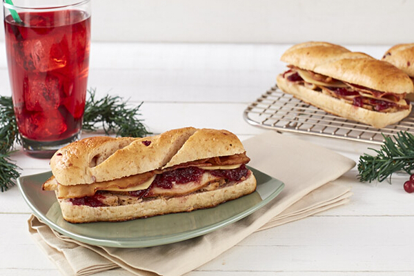 Roasted Turkey and Chicken with Bacon on Cranberry Bread (P175). Slow cooked chicken and turkey marinated in rosemary, thyme, and sage; thick cranberry sauce; and honey-cured bacon are served on crusty cranberry bread.